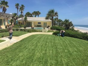 Two men doing yard maintenance at a Jacksonville beach house