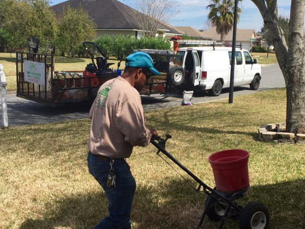 A Pyramid Lawn Service employee seeding a front yard